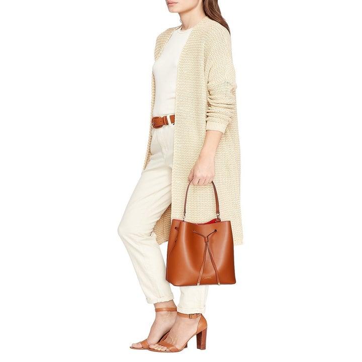 A model holding the bag in Lauren Tan/Monarch Orange/Gold