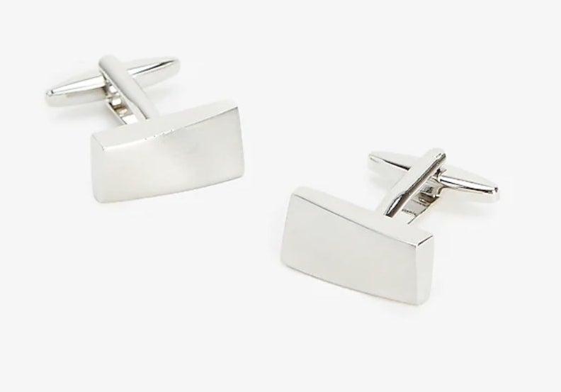 A pair of silver cufflinks in an imperfect rectangular shape