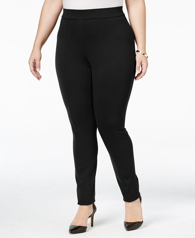 Front view of a model wearing the seamed leggings in black