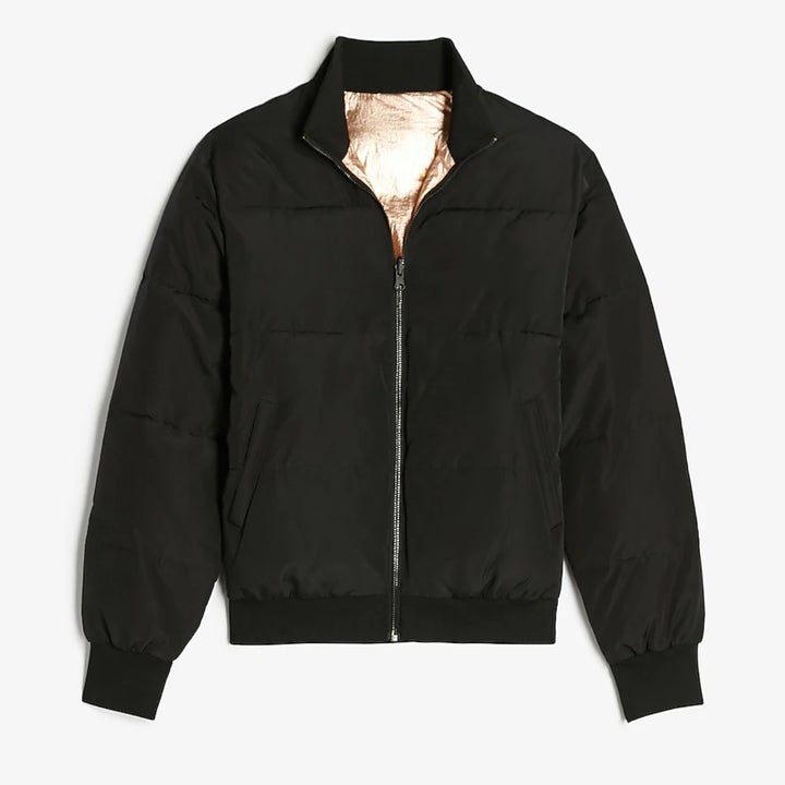 A black bomber. jacket with a metallic fabric on the inside