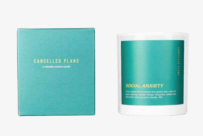 """A teal-colored candle that says """"social anxiety"""" on it"""
