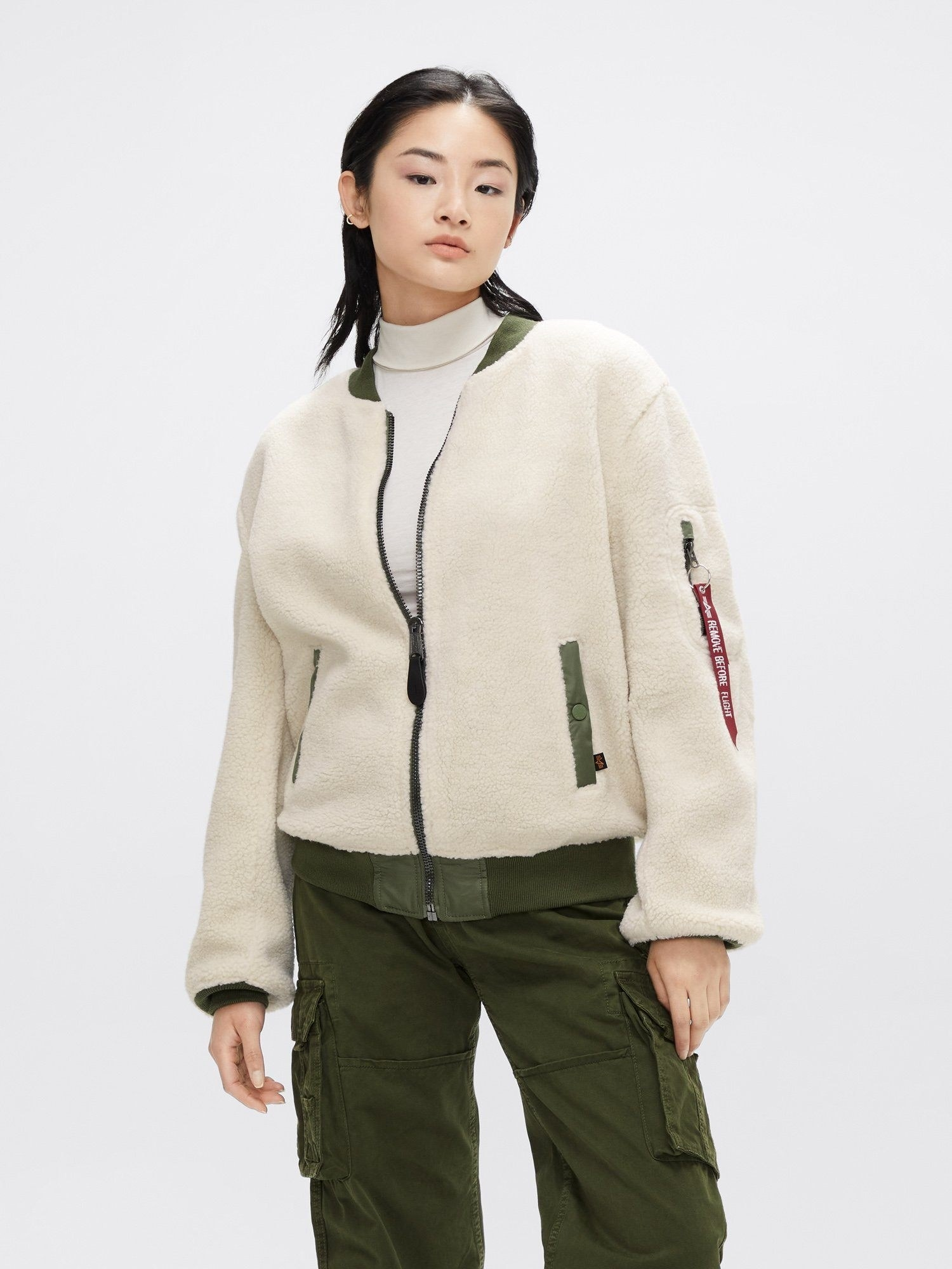 A model wearing the sherpa bomber in light cream