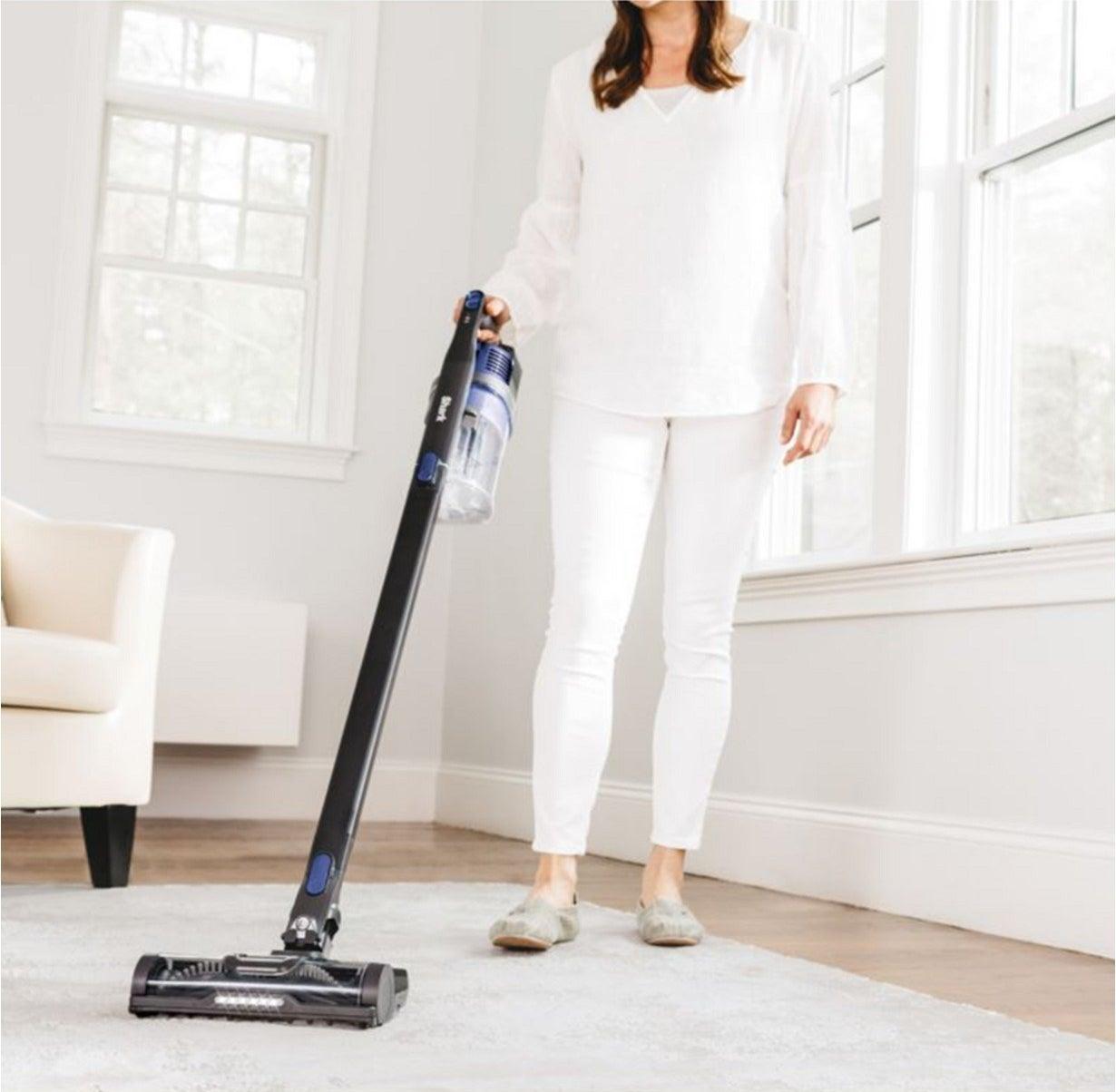 A model using the stick vacuum vacuum on a carpet
