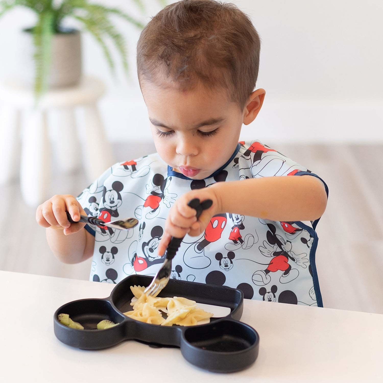 Child eating while wearing tee style smock with short sleeves and food-catching pocket in center