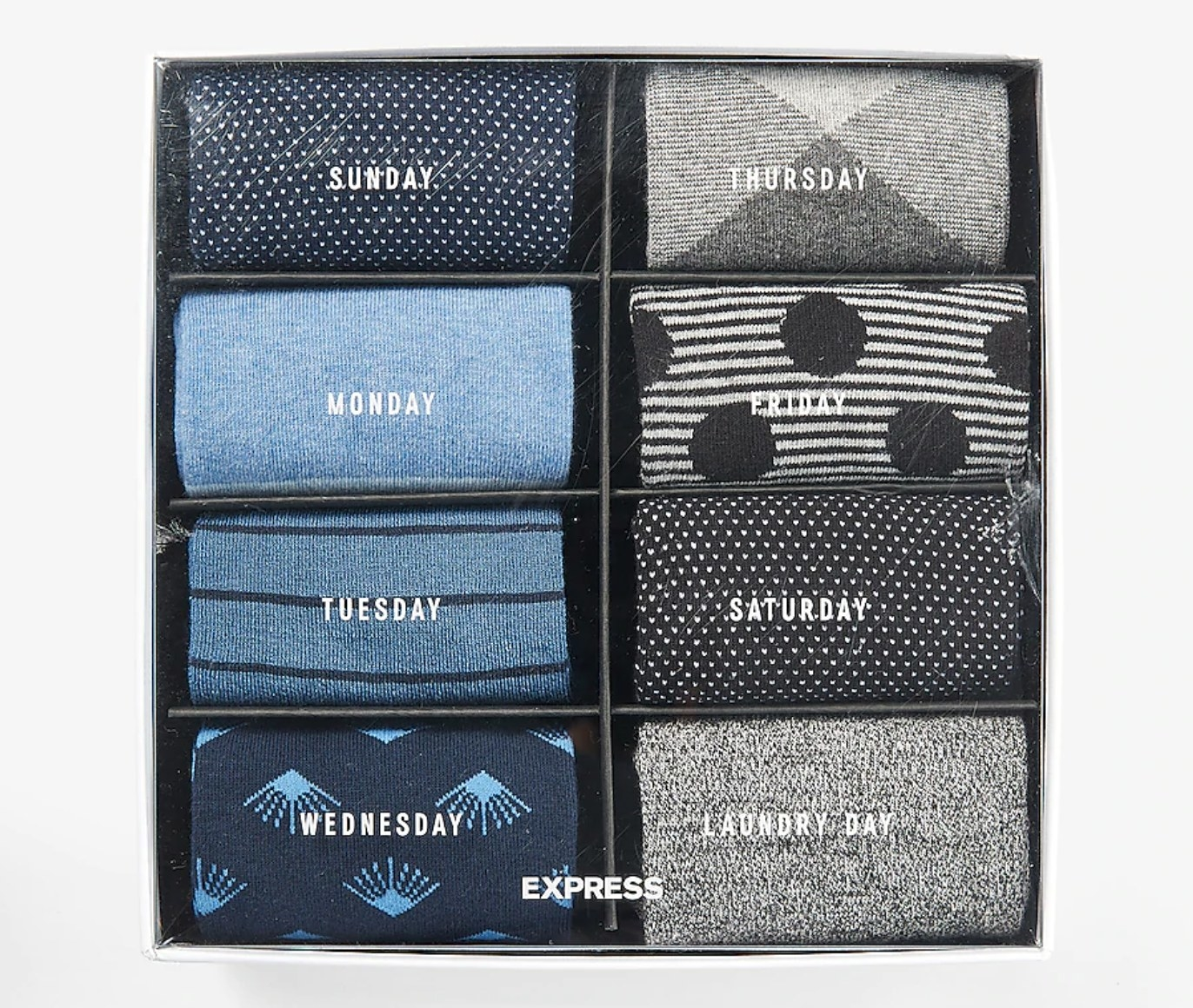 """A box of eight socks in black, gray, white, and blue with the days of the week on it, and an eighth one with the words """"laundry day"""" on it"""