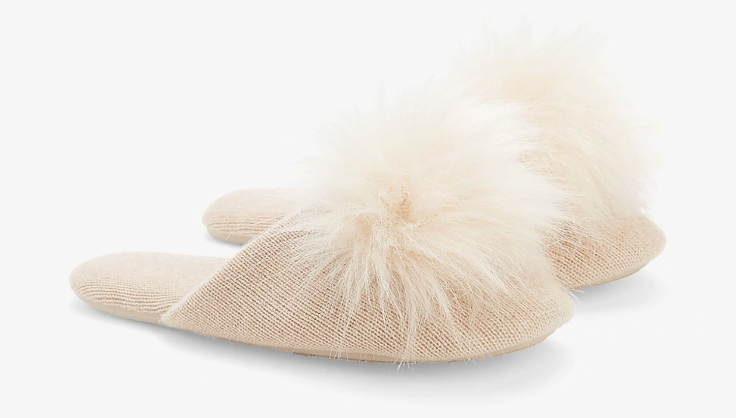 A cream-colored pair of slippers with a pom on each