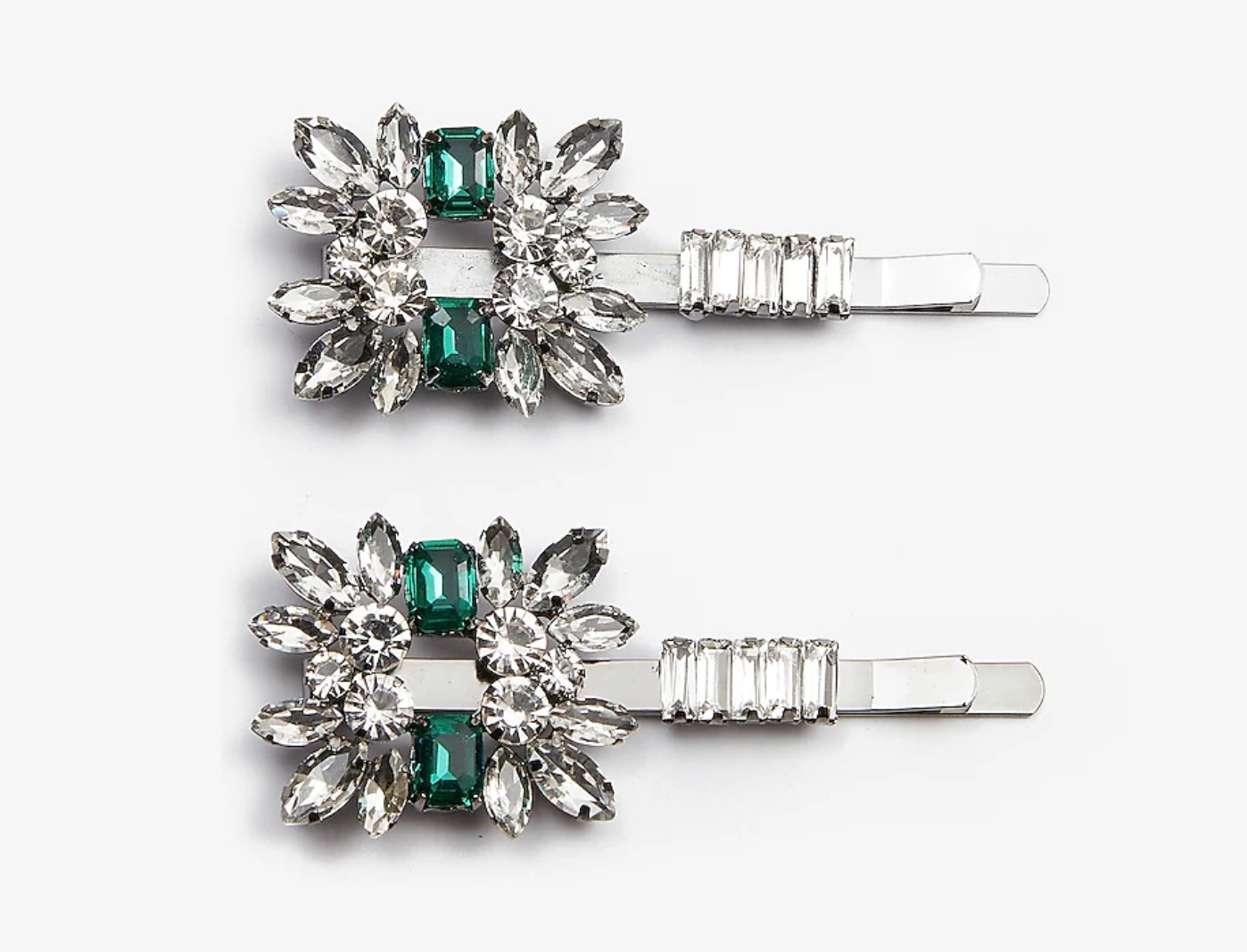 A pair of silver hair clips with diamond-like an emerald-like gems on it