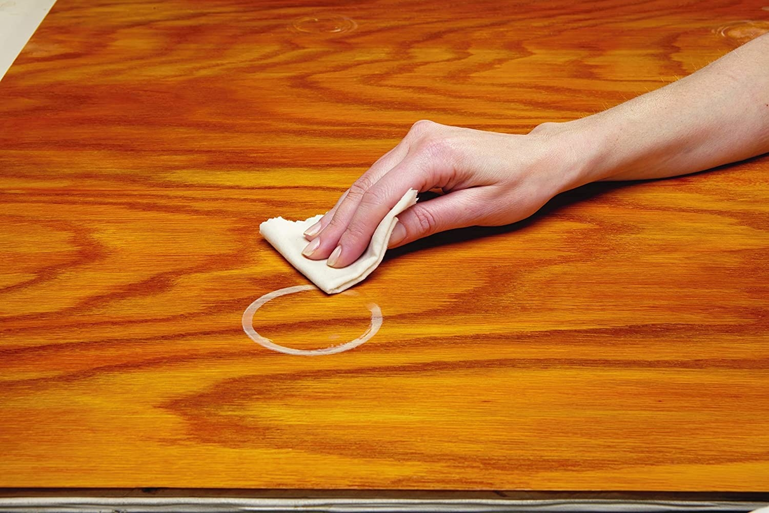 The wipe removes a stubborn coffee cup ring from a wooden table