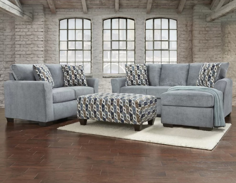 Blue-gray love seat with patterned pillows, patterned ottoman, blue-gray sectional with patterned pillows