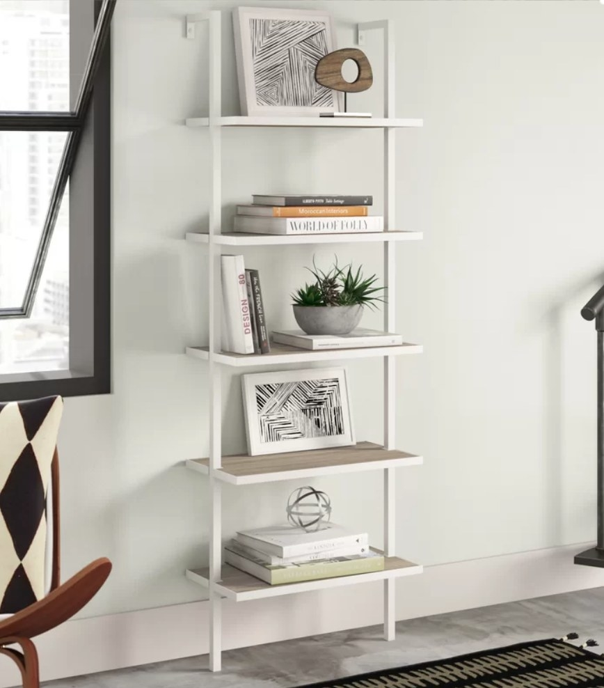 White 5 tiered bookcase with various books, frames and decorative items