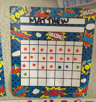 Comic strip themed graph chart with child's name and stickers. There are space to write the days of the week and seven days with five week's worth of spaces.