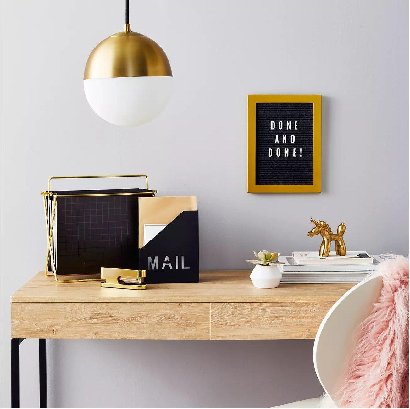 Black and gold letterboard above desk