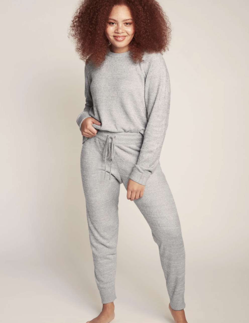 Model wearing the crewneck sweater and track pants in light grey