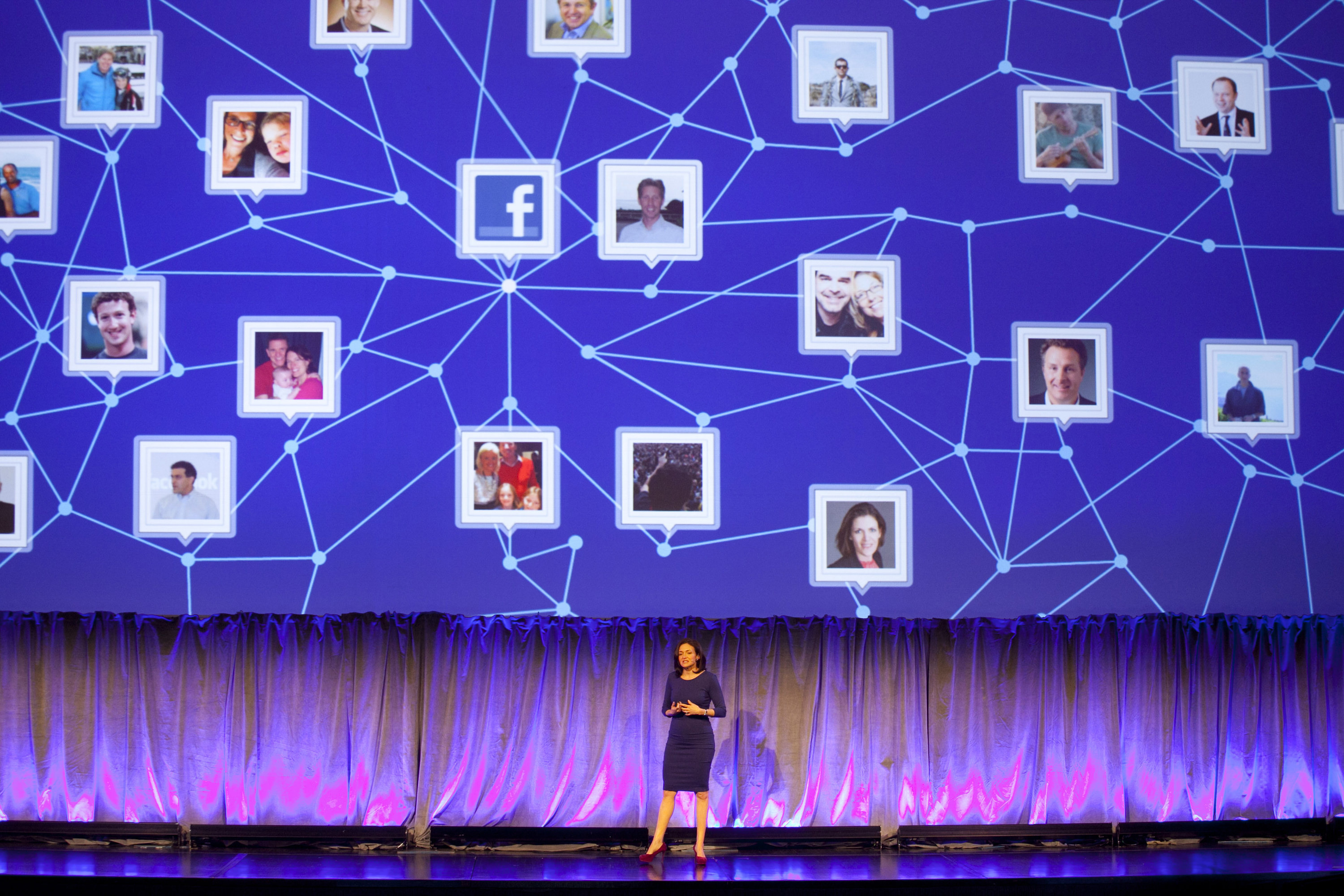A woman speaks onstage in front of a large diagram above her that shows images of people connected to one another by lines, resembling a vast social network