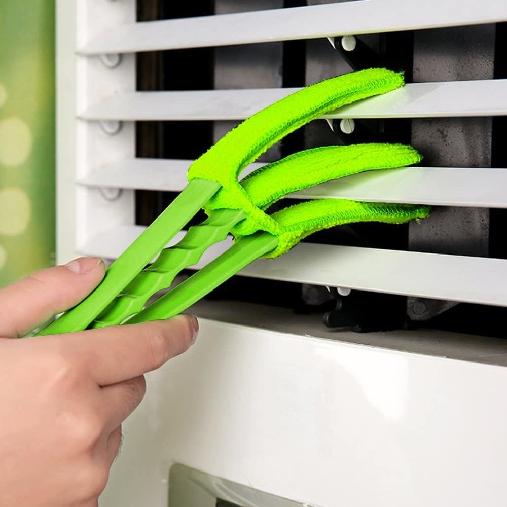A hand using the blind duster to clean blinds