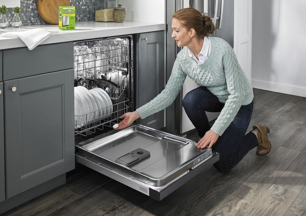 A model inserts a tablet into the dishwasher