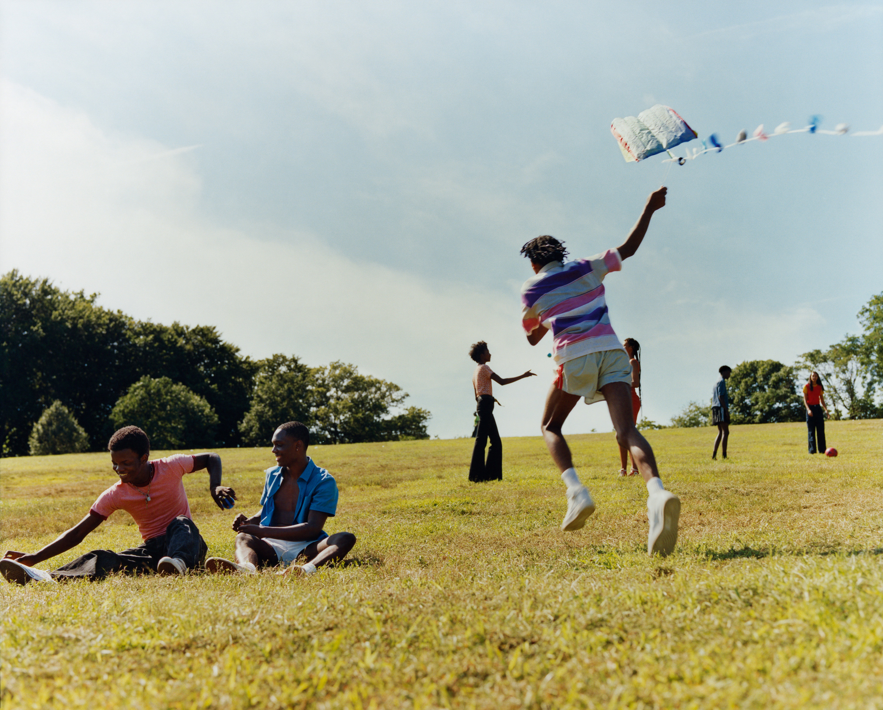 Young teenagers running and playing in a field under a blue sky.