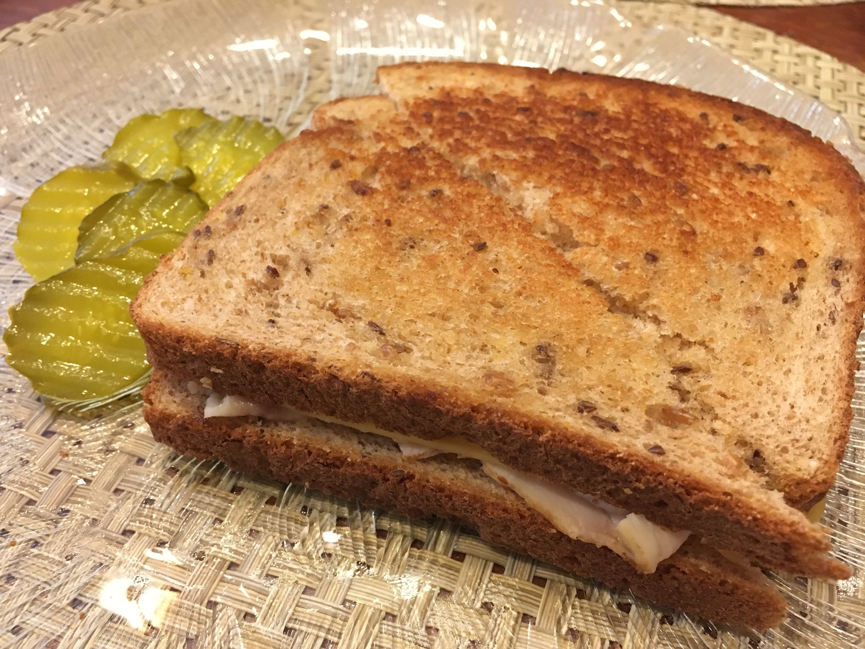 A simple toasted sandwich with two pickle slices