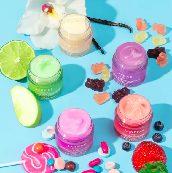 Several jars of the lip mask arranged on a colourful background surrounded by candy and fresh fruit