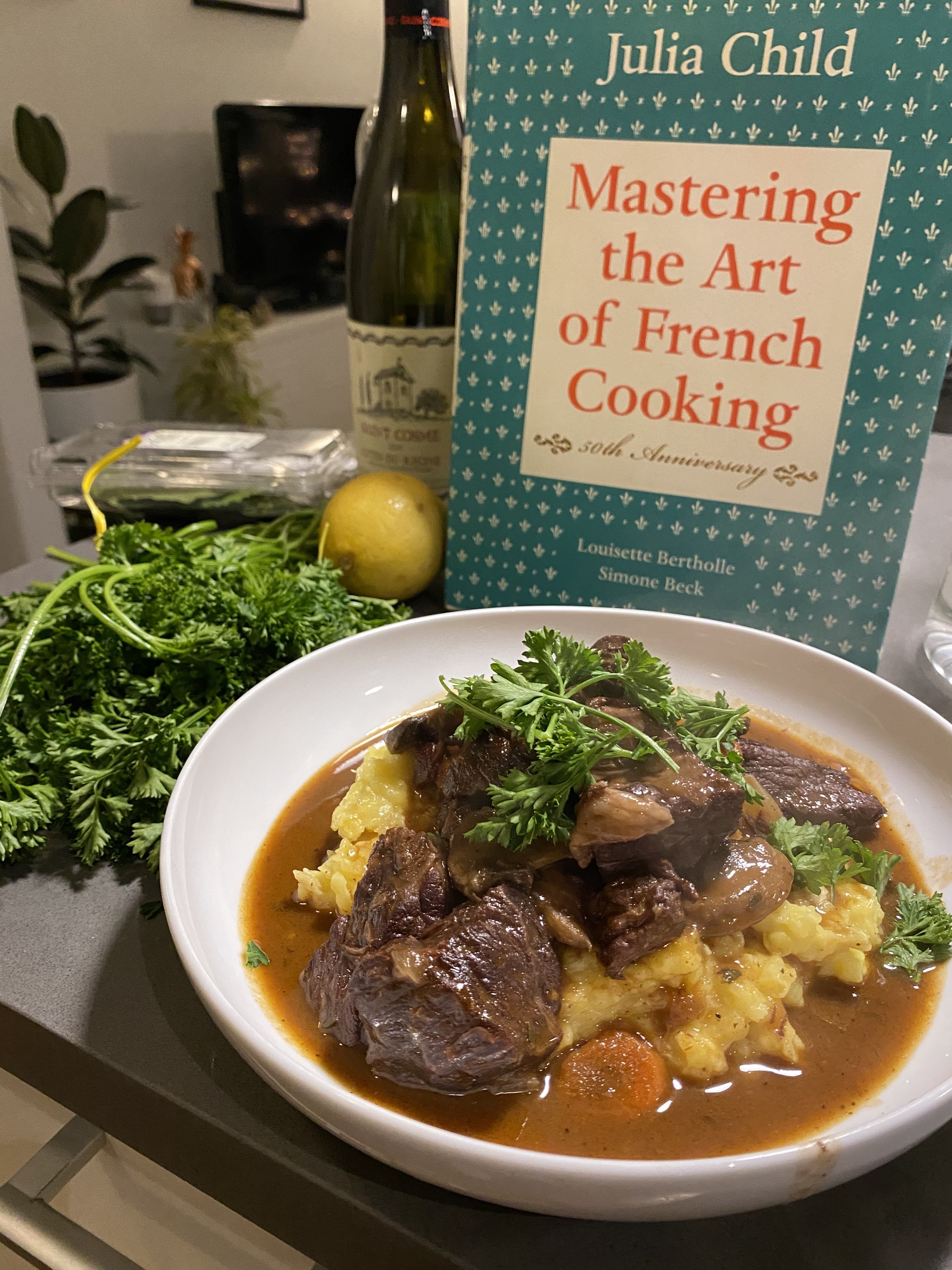 "A copy Julia Child's book ""Mastering the Art of French Cooking"" is seen behind a large plate of food"
