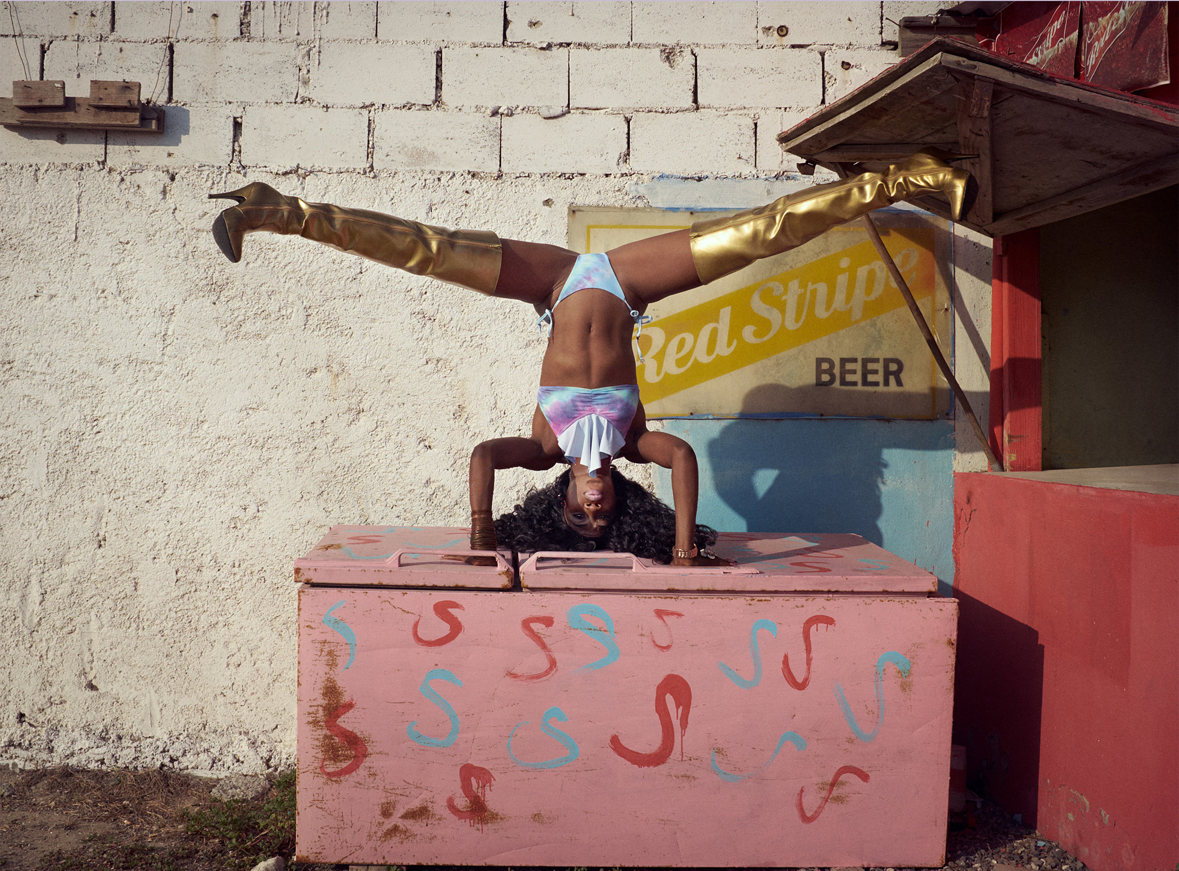 A woman in gold boots doing a handstand on a pink box