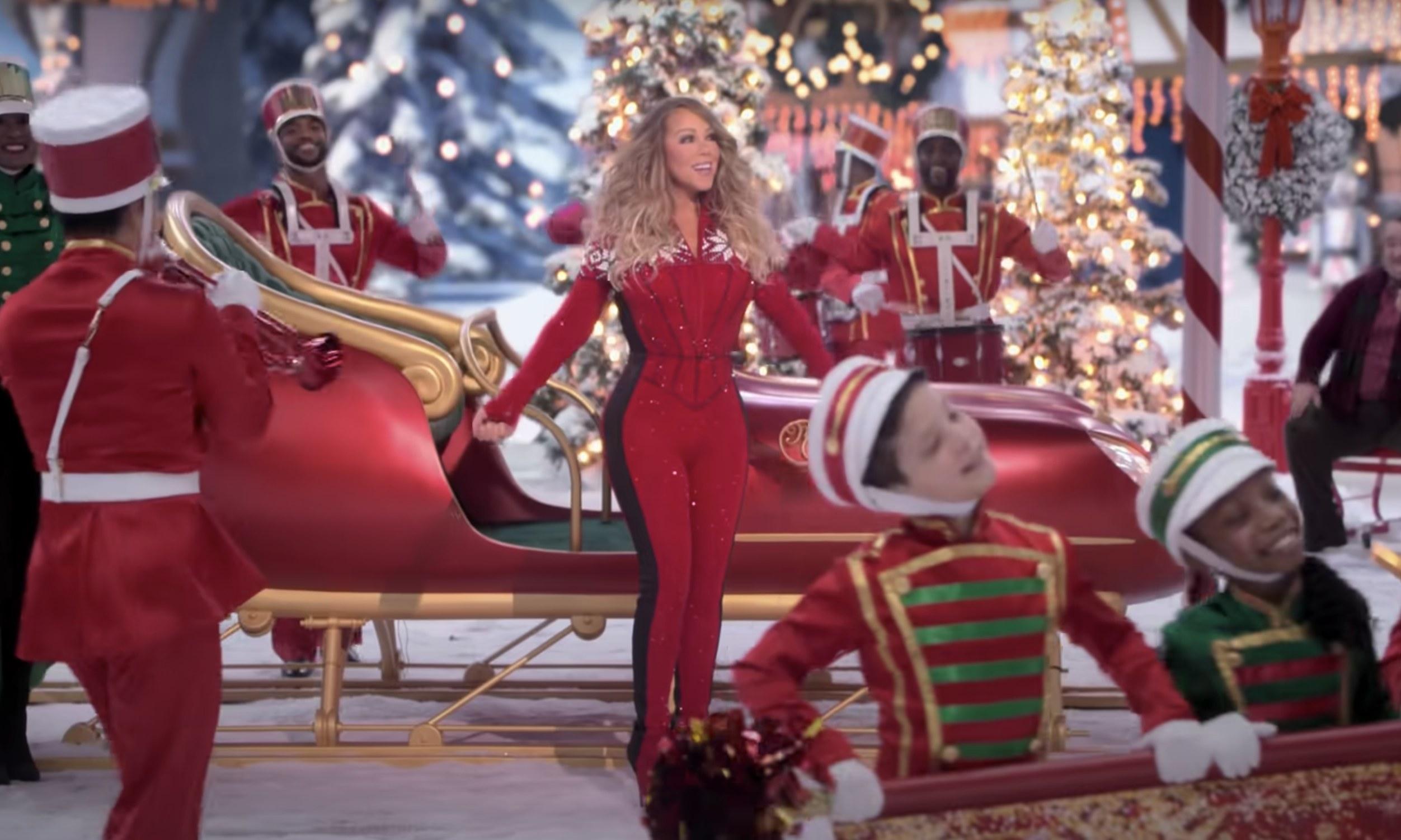 Mariah Carey singing next to a sleigh
