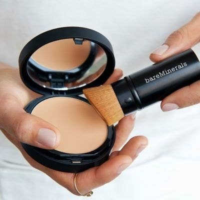 a hand holding the brush to powder foundation