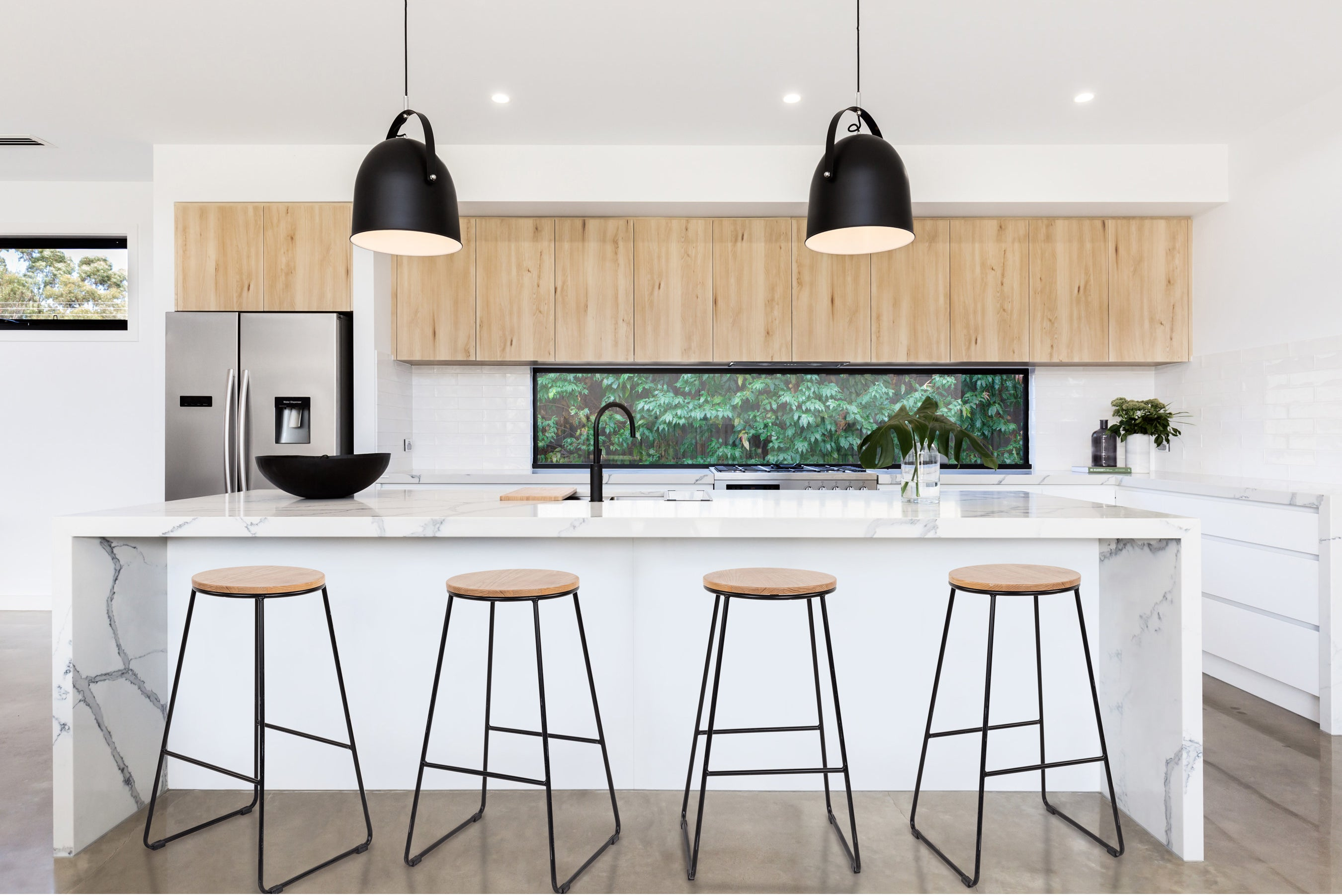 the four stools with a black metal bottom and round wood top displayed in a kitchen