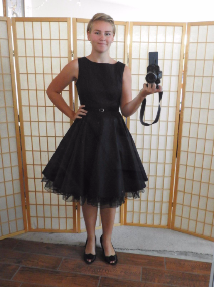 a reviewer wearing the black dress with heels