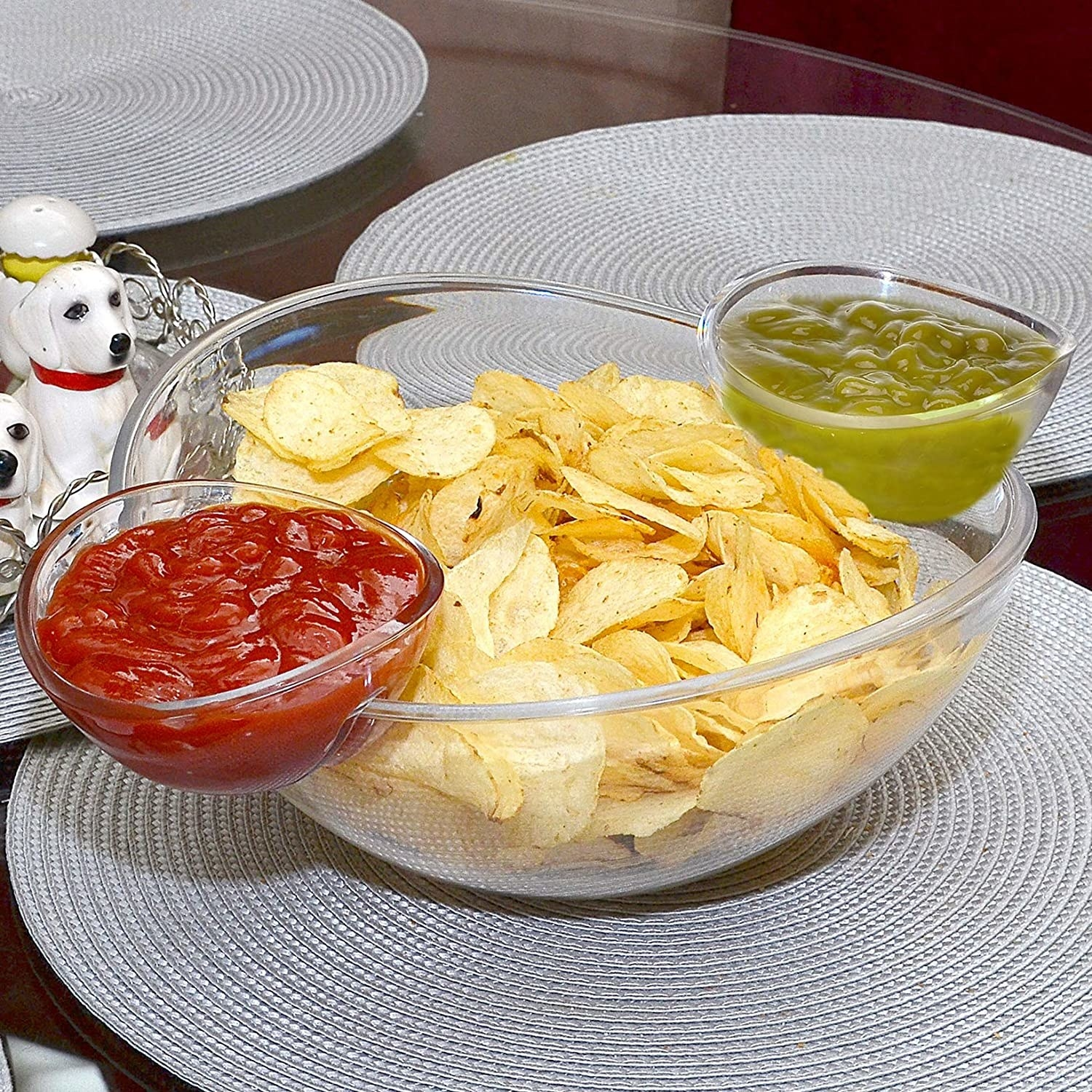 chip bowl filled with potato chips and two condiment holders filled with a ketchup and a green dip