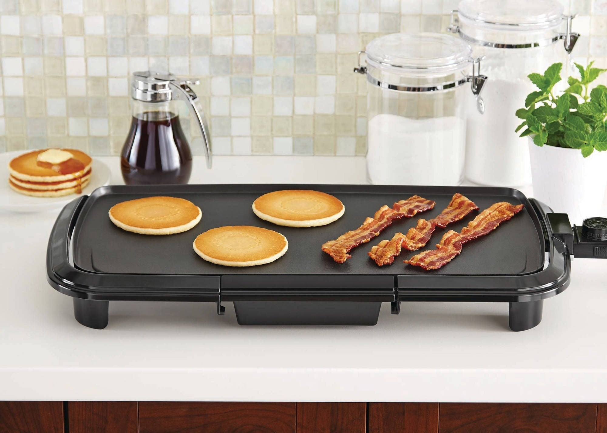 the griddle in the color black with pancakes and bacon on top of it