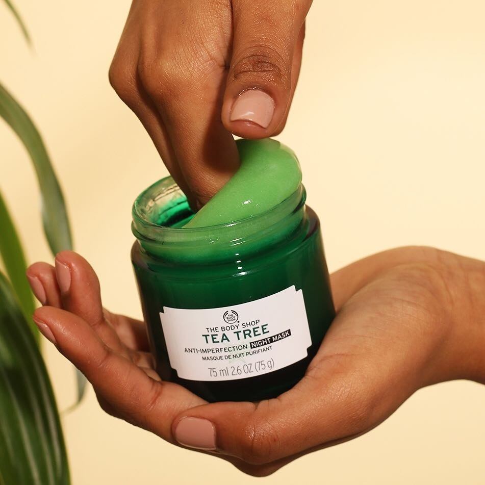 Hand digging into green jar of product