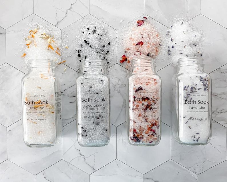 four different bottles pouring out bath salts