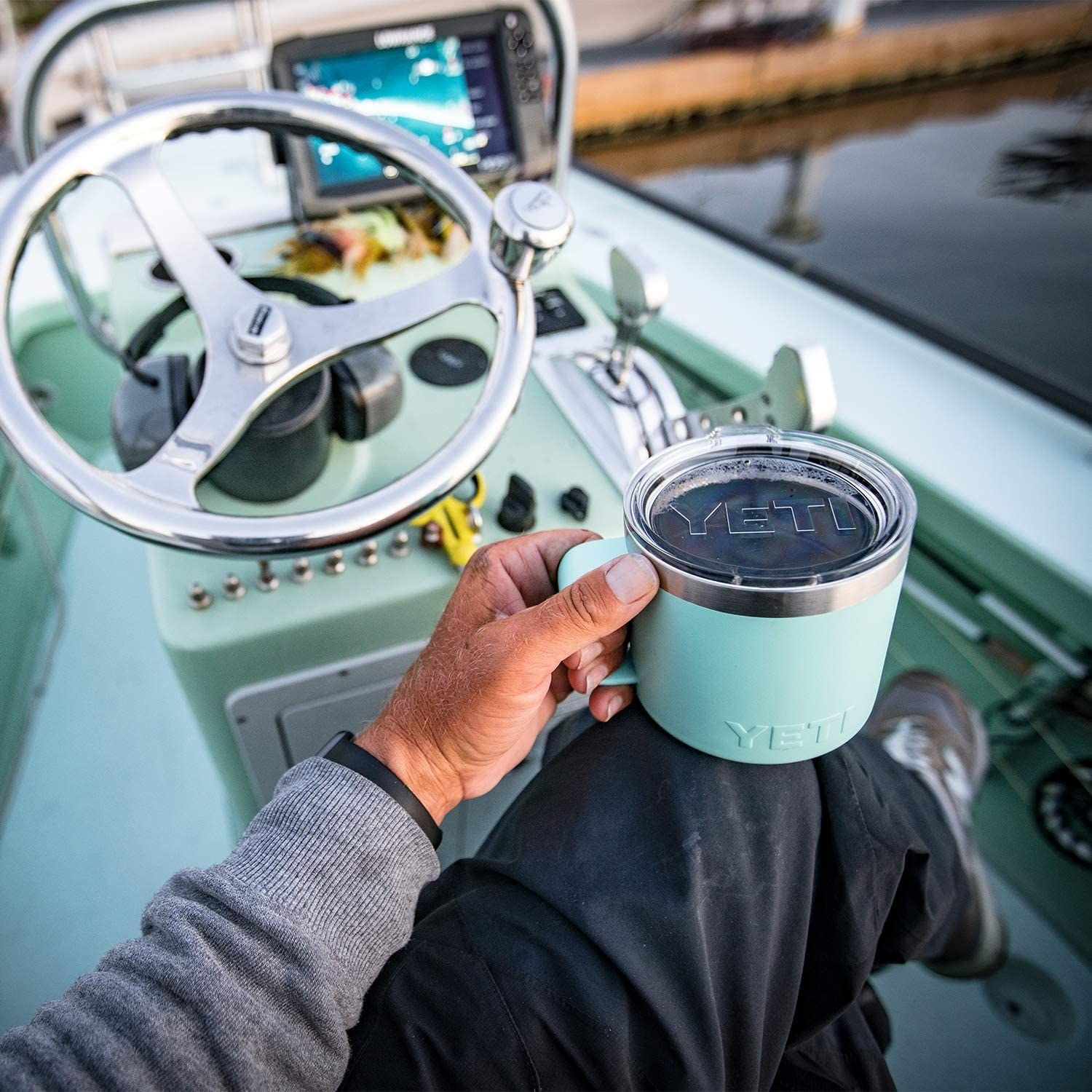a model holding a mint green yeti mug while sitting on a boat