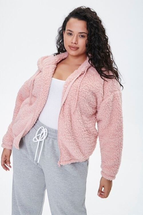 a model wearing the hoodie in light pink