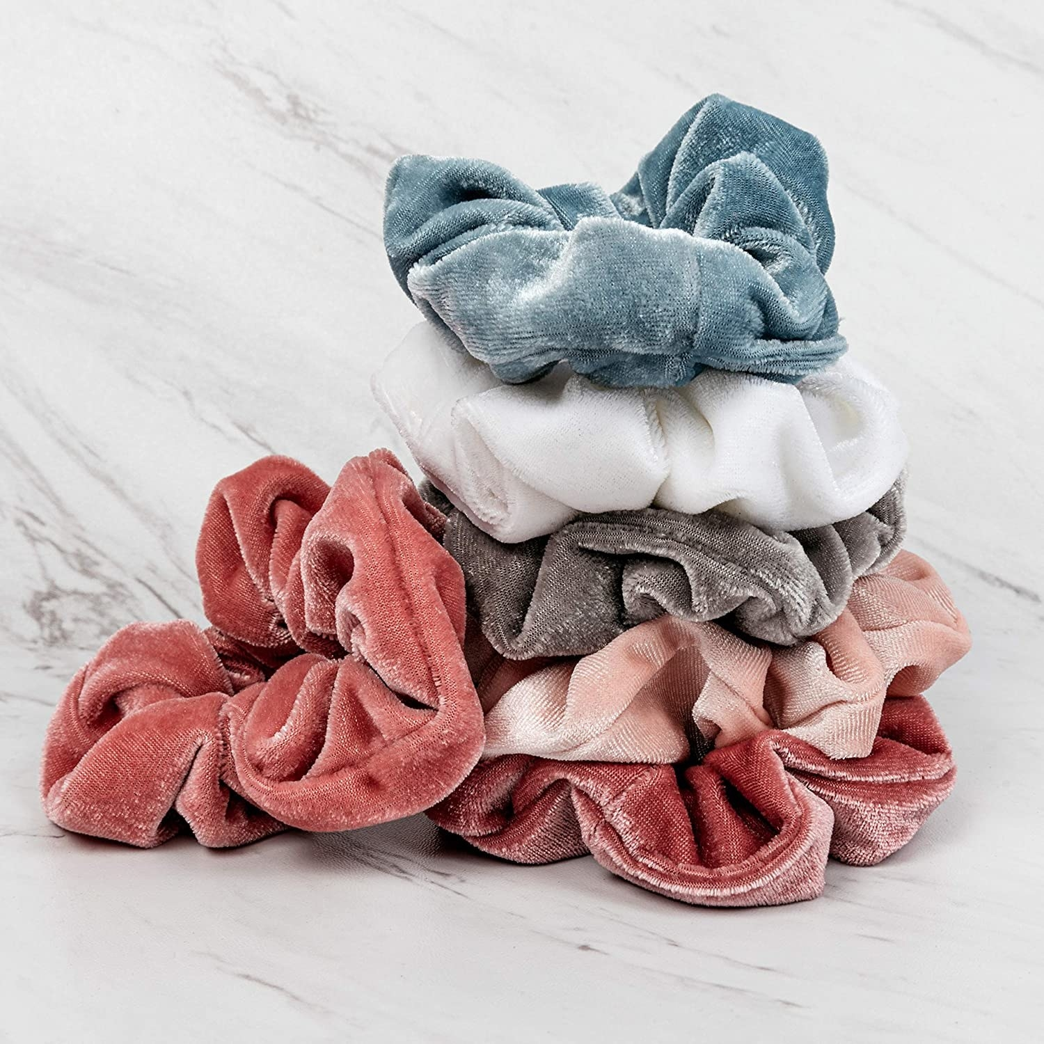 a stack of pink, gray, white, and blue velvet scrunchies