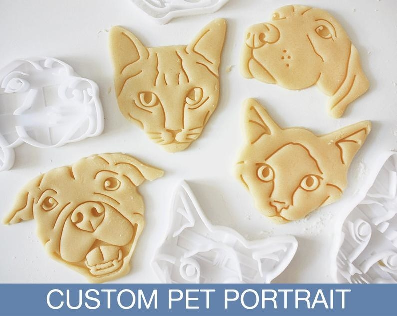 Four raw cookies made with the cookie cutters in the shape of two cats and two dogs