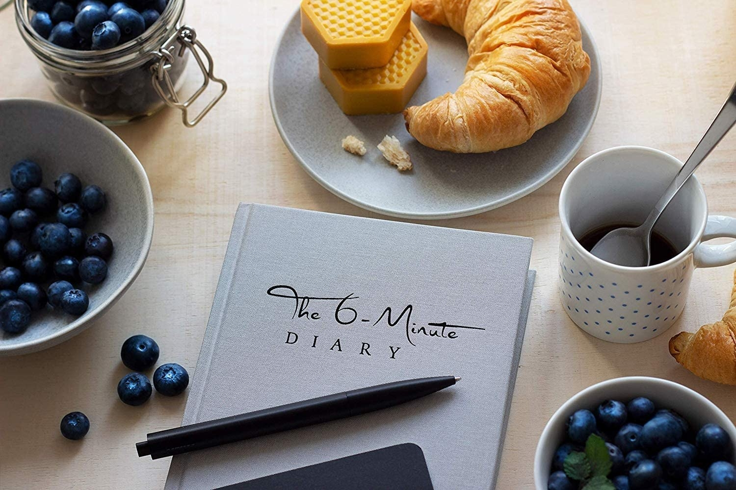 A flatlay of the journal next to a bowl of blueberries and a croissant