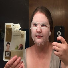 a reviewer holding a face mask and wearing the sheet mask