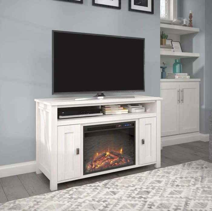 A white TV stand with electric fireplace and heater and storage cabinets