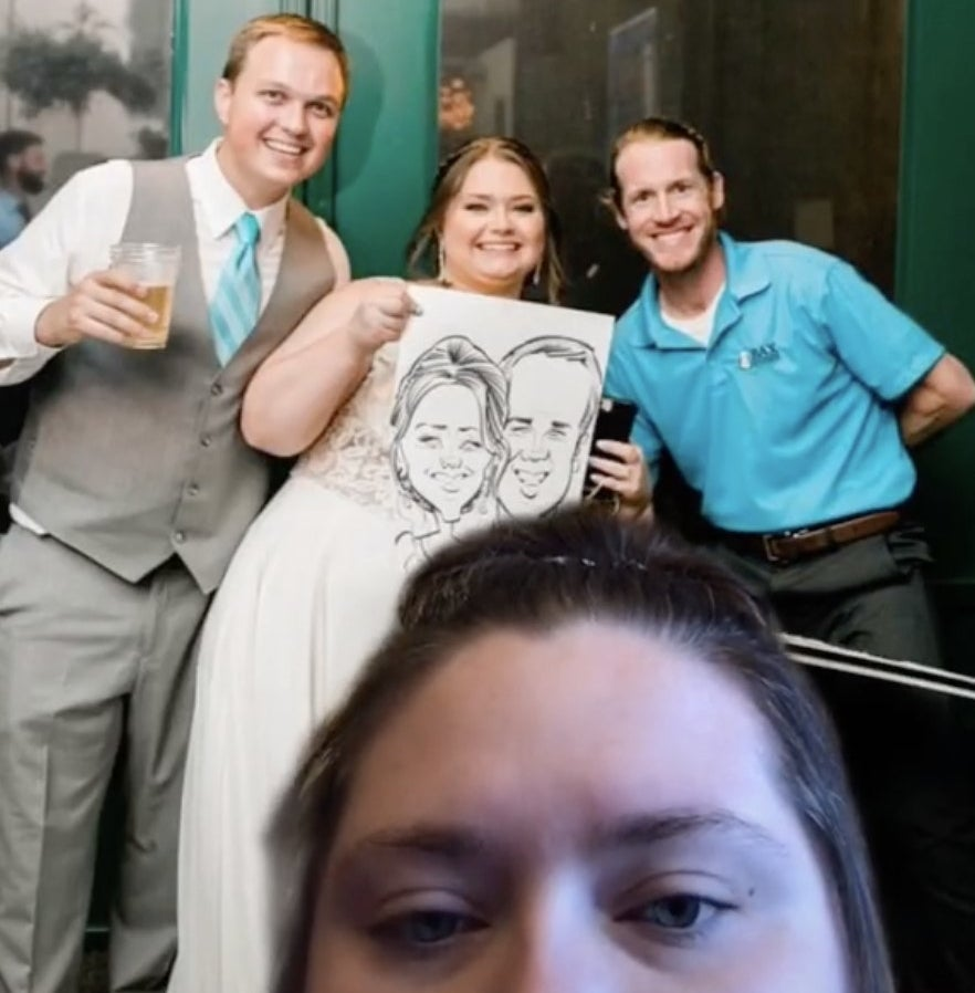 A bride and groom hold up a caricature next to the artist