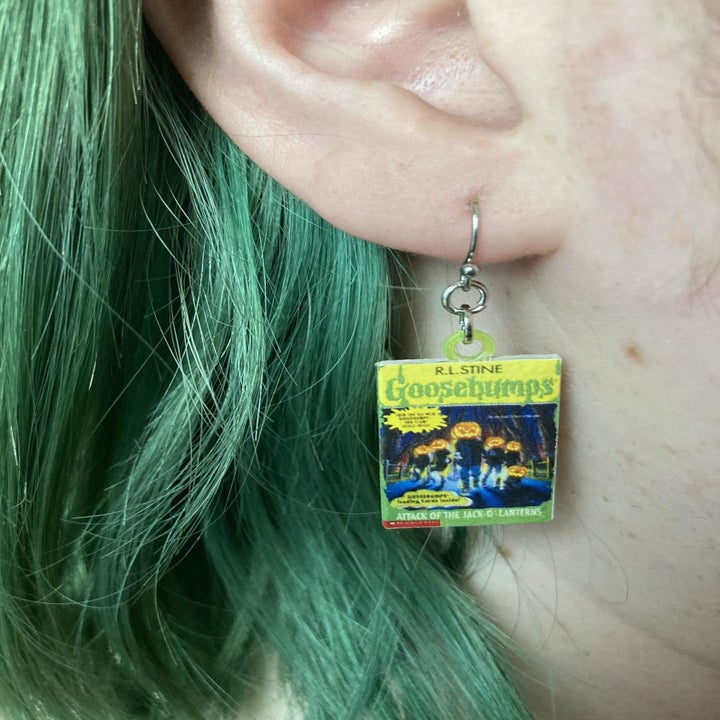 """close-up of model wearing earrings with the """"Attack Of The Jack-o-lanterns"""" Goosebump books"""