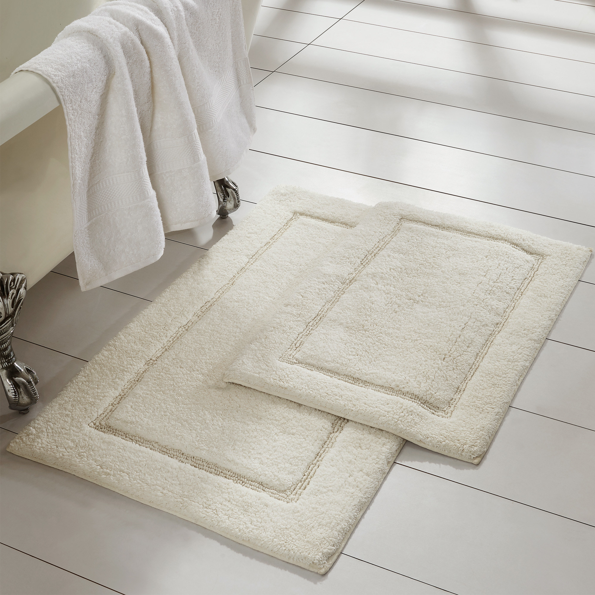 a big and small rug in the color ivory laid out on a bathroom floor