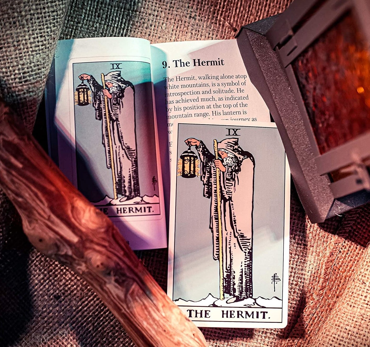 The Hermit tarot card next to its meaning described in a book