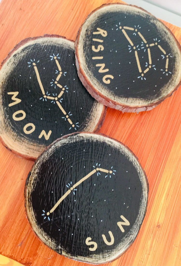 """wood cross-section coasters painted with constellations and """"sun,"""" """"moon,"""" and """"rising"""""""