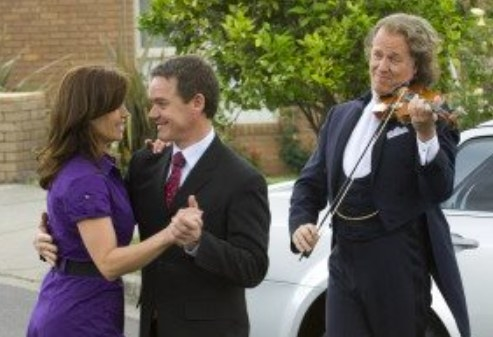 André Rieu plays the violin as Paul and Rebecca dance in the street