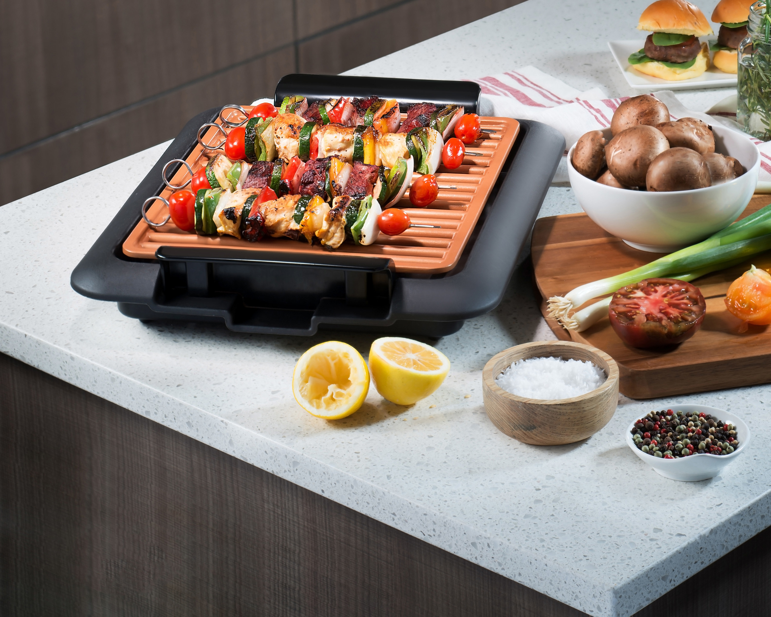 the grill displayed indoors being used to grill chicken and vegetable skewers