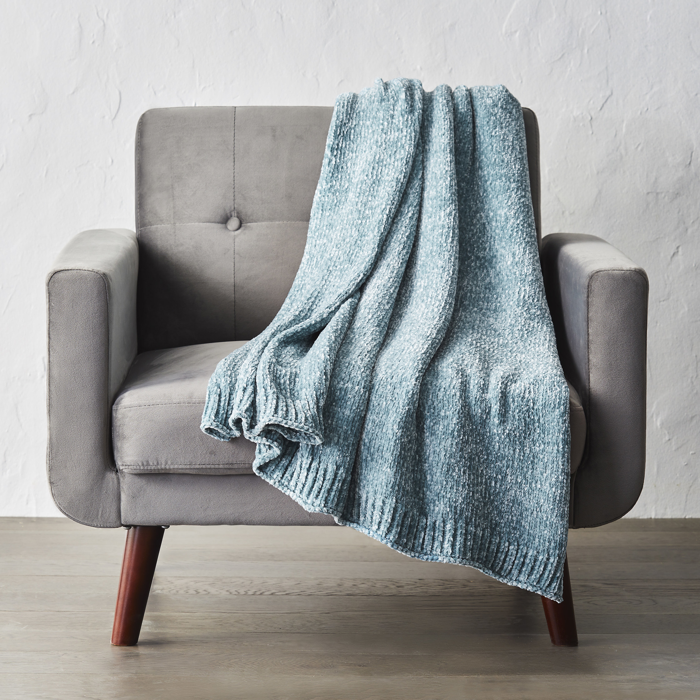 the throw in blue draped over a couch