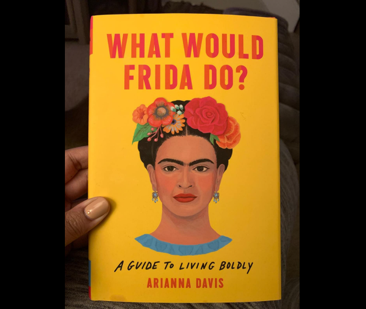 The yellow book cover featuring a painting of Frida on it
