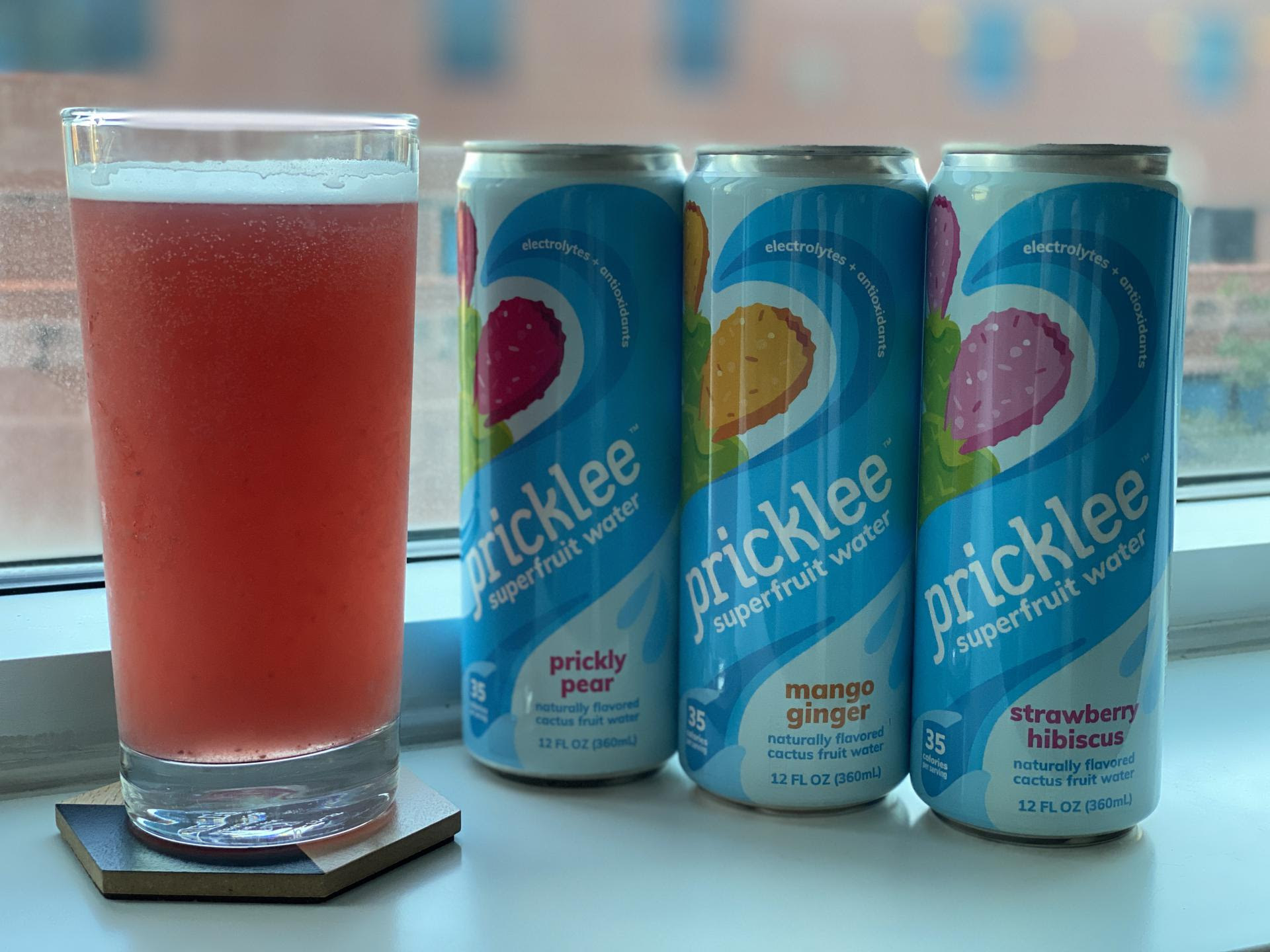 cans of pricklee fruit water next to one that's a dark pink color poured into a glass